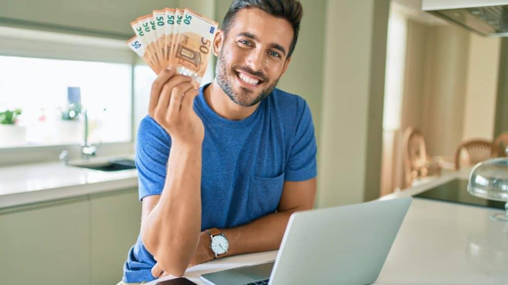 Homme gagnant de l'argent avec son ordinateur