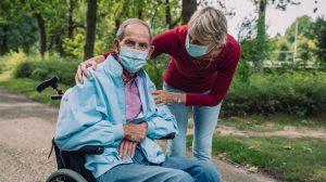 Auxiliaire s'occupant d'un homme en fauteuil