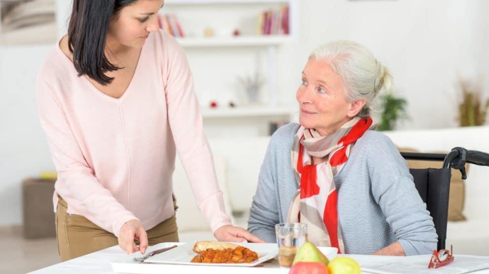Auxiliaire de vie apportant son repas à une personne agée